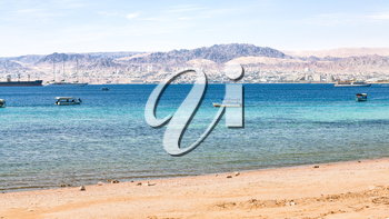 AQABA, JORDAN - FEBRUARY 23, 2012: urban beach of Aqaba and view of Eilat city in the background in winter. Jordan country has only one exit to sea in Gulf of Aqaba, the length of the coast is 27 km