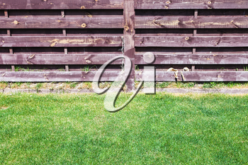 clipped lawn near wooden fence on backyard of country house