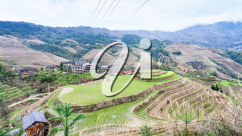 travel to China - view of village and viewpoint Golden Buddha Peak in terraced fields from Seven Stars Chase The Moon in Dazhai area Longsheng Rice Terraces (Longji Rice Terraces) country in spring