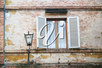 travel to Italy - lantern near window of medieval house in Siena city in winter