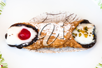 top view of typical sicilian pastry Cannolo sprinkled with confectioner's sugar on white plate