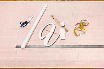 top view of tools to draw a clothing pattern on sheet of graph paper