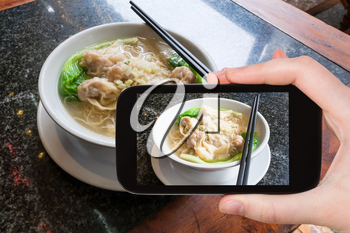 travel concept - tourist photographs local chinese soup Dim sum with noodle in cafe in Yangshuo County in China on smartphone