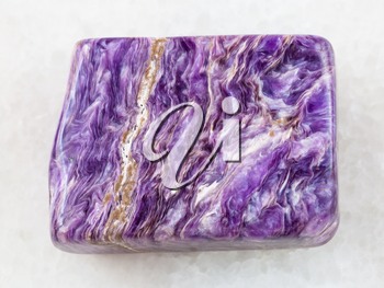 macro shooting of natural mineral rock specimen - polished slab of charoite gemstone on white marble background from Murun Massif, Yakutia, Russia