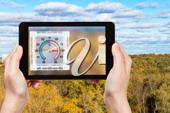 travel concept - tourist photographs city park and outdoor thermometer on home window in hot autumn day on smartphone in Moscow, Russia
