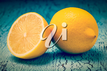 Vintage retro effect filtered hipster style image of lemon and cut half slice on blue wooden background
