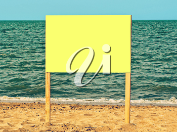 Yellow blank billboard on sandy beach against of sea surf.Just add your text.