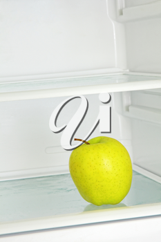 Lifestyle concept.Yellow apple in domestic refrigerator taken closeup.