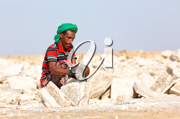 ETHIOPIA,DANAKIL-CIRCA  DECEMBER 2017--unidentified man working the block of salt