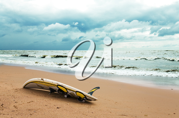 Board for windsurfing on the beach and cloudy sky