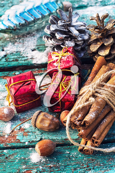 Gifts and decorations for Christmas on wooden background strewn with pine cones and spices