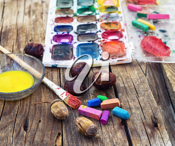 set of different paint colors and  brush for painting on wooden background in the autumn style