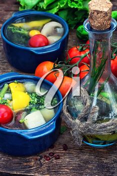traditional soup of fresh vegetables in blue pot on wooden background.Photo tinted