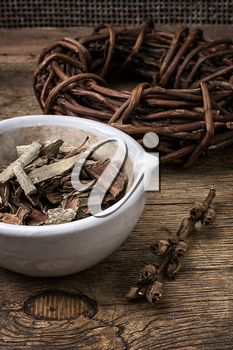 medicinal licorice rolled in  coil and aspen bark on wooden background.Selective focus