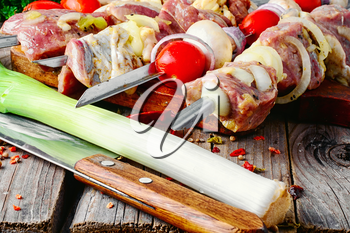 raw meat with vegetables threaded onto a skewer for roasting on the coals