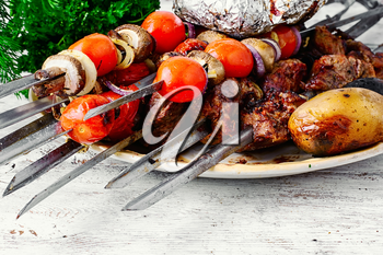 Beef cooked with vegetables on skewers and baked potatoes