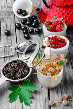Fruit tea with raspberries,currants in the red stylish kettle