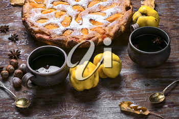 Autumn pie with slices of quince and warming cup of tea