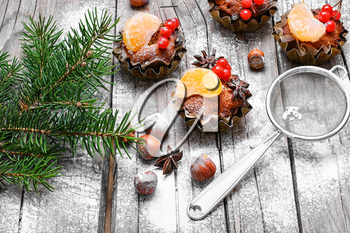 little cupcakes in tins ,decorated with berries and a slice of tangerine