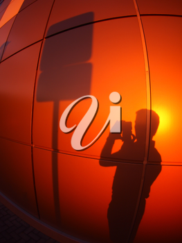 The silhouette of a man on a red-orange wall, who photographs a road sign in the evening at sunset with wide angle fisheye lens and distortion view