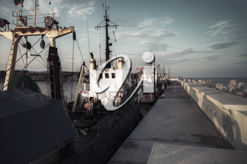 Industrial fishing boats are moored in port of Nesebar, Bulgaria. Dark vintage tonal correction filter, retro style effect