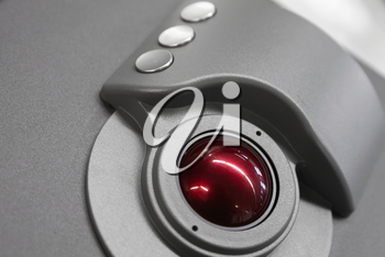 Industrial control panel made of gray metal with red trackball, close up photo with soft selective focus