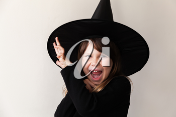 Laughing little blond girl in black witch costume posing over white wall, close-up studio portrait