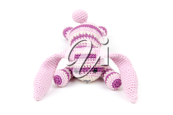 Sad knitted rabbit toy lays isolated on white background