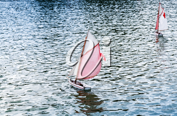 Traditional small wooden sailing toy boats in the pond of park Jardin du Luxembourg, Paris, France