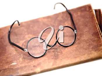 Old glasses on the leather folder isolated on white