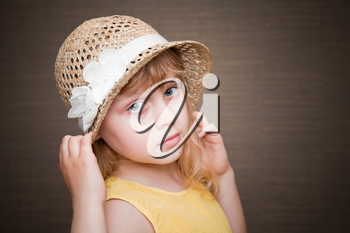 Portrait of a little blond girl with nice straw hat