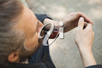 Man smoking pipe, outdoor photo with selective focus