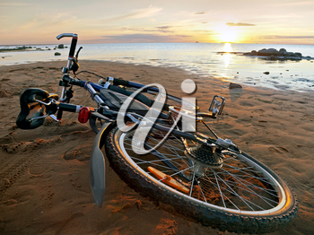 At the end of a journey. Bicycle lying on the beach in the light of setting Sun