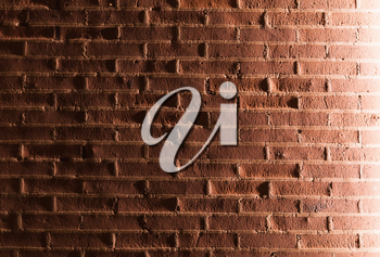 Red painted brick wall with side illumination effect. Background photo texture