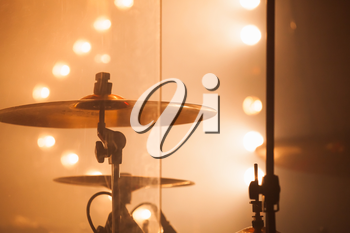 Warm toned musical photo background, cymbals as a part of  rock drum set  over blurred stage lights