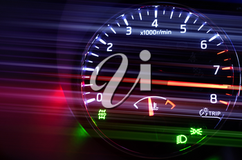 Closeup photo of modern automotive tachometer with hi speed on black background, motion blur filter effect