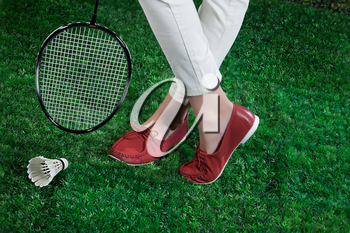 Woman's legs, badminton racket and shuttlecock on a green grass