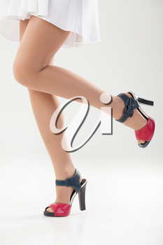 Woman's legs in shoes on isolated background