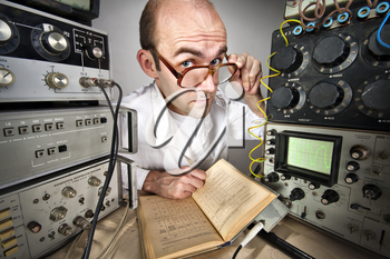 Pensive scientist reading book at vintage technological laboratory
