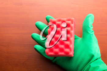 Green cleaning glove with a sponge on the table