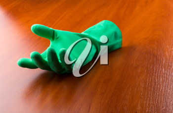 Green cleaning glove on the wooden table