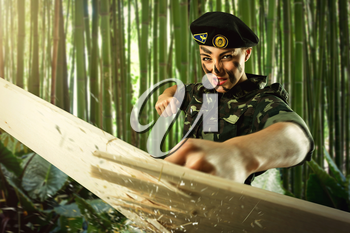 Strong army soldier woman is hiting wooden board