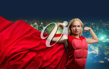 Strong woman superhero showing off her strength against night city background