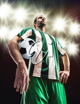 Football player holding a ball against light