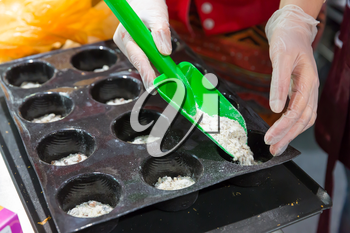 Close up of woman hand putting dough in forms for baking