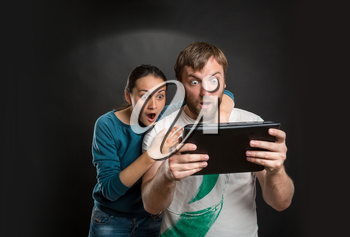 Very excited man and woman playing with tablet
