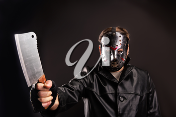 Murderer in hockey mask holding meat cleaver in hand, dark background
