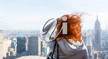 Young woman looking at the cityscape from observation deck. Blur city on background.