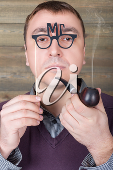 Young man with funny glasses on a stick and smoking pipe in hand, wooden background. Fun photo props and accessories for shoots