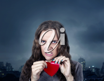 Young female with angry face holding red heart on a stick in her hands, night city on background. Fun photo props and accessories for shoots
